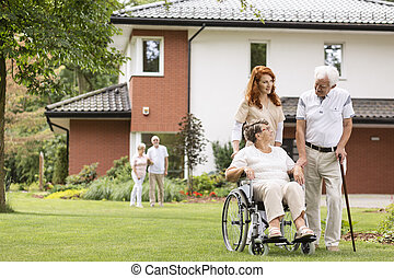 An elderly woman on a wheelchair and her husband with a cane with their medical assistant outside in the garden of a private care home.