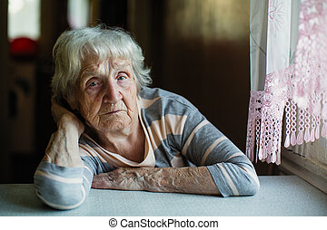An elderly woman pensioner sits sadly near the window.