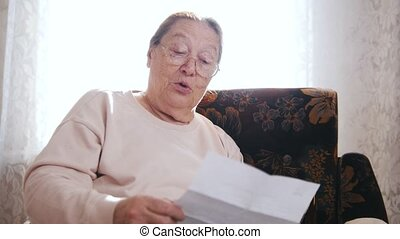 An elderly woman reading letter aloud while sitting in a chair on the background of the window.