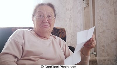 An elderly woman reading letter while sitting in a chair on the background of the window.