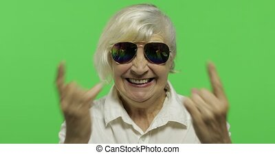 An elderly woman show sign of the horns with her hands....
