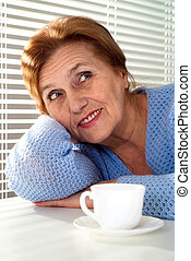 An elderly woman sits at a table