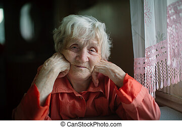An elderly woman sits near the window in house.