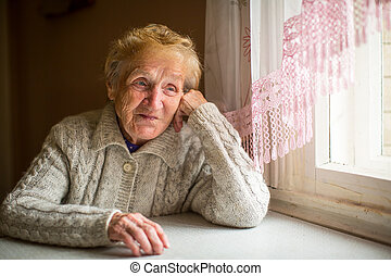 An elderly woman sits near