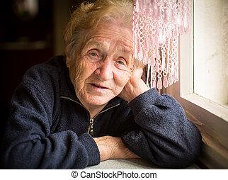 elderly woman sits near the window