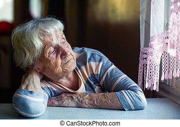 An elderly woman sits sadly near the window.