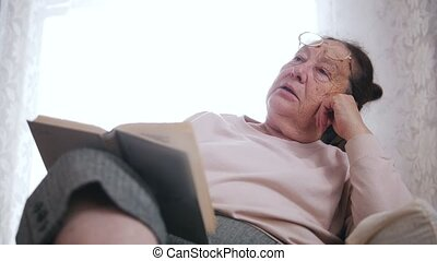 An elderly woman sitting in a chair and closies book on the...