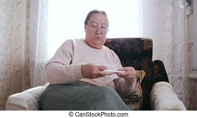 An elderly woman sitting in a chair and holds paper in hands...