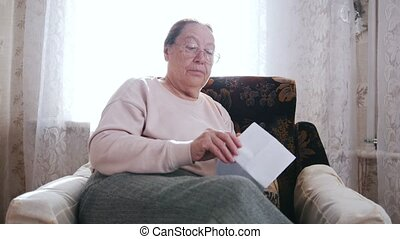 An elderly woman sitting in a chair and opens a letter on the background of the window.