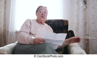 An elderly woman sitting in a chair and reading letter aloud on the background of the window.