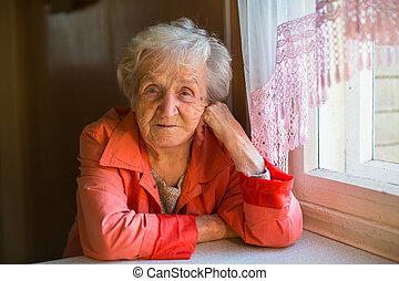 An elderly woman sitting near the window.