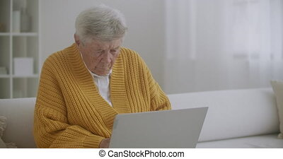 An elderly woman sitting on the couch prints a message on the keyboard. Grandma uses a laptop. High quality 4k footage