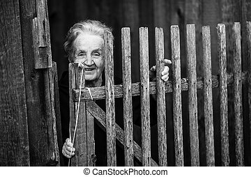 An elderly woman stands near a wooden fence