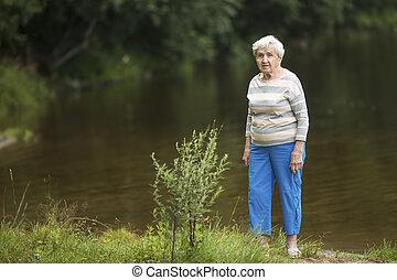An elderly woman stands