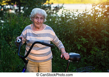 An elderly woman stands with a bicycle.