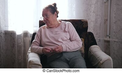 An elderly woman talks while sitting in a chair and knitting...