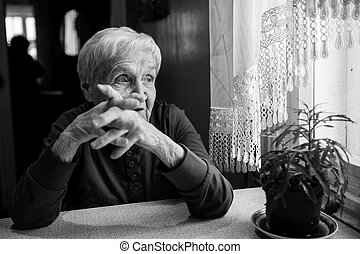 An elderly woman thinking near the window. Black and white photo.