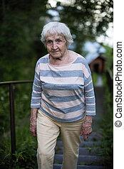An elderly woman walking outdoor.