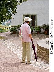 An elderly woman walks