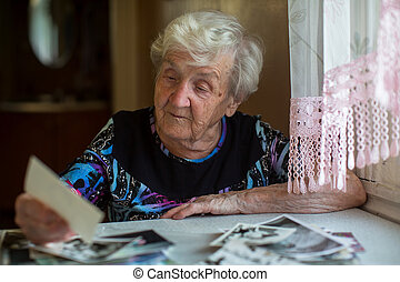 An elderly woman watching photos sitting at the table.
