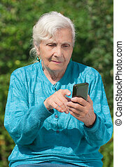 An elderly woman with a modern mobile phone in the hands