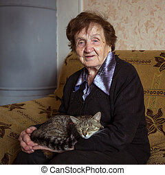 An elderly woman with cat in her home.