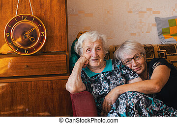 An elderly woman with her adult daughter sitting in an embrace on the couch.