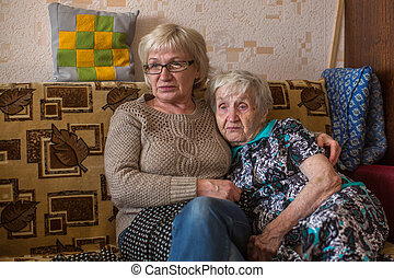 An elderly woman with her adult daughter watching the news on TV.