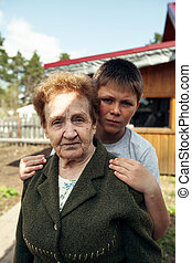 An elderly woman with her grandson outdoors in the village.