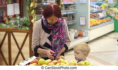 An elderly woman with her little grandson buy fresh apples in a supermarket.