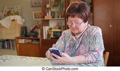 An elderly woman writes a text message on her mobile phone. She carefully presses on the screen and pronounces the text.
