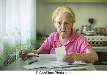 An elderly woman writes