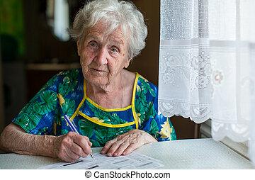 An elderly woman writes the bills