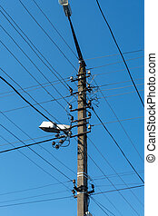 an electric post in with lots of wires