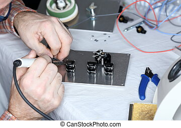 an electrical worker is soldering