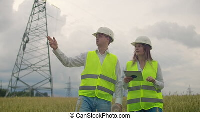 An electrician in the fields near the power transmission...