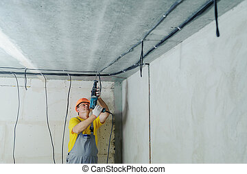 An electrician is drilling a ceiling with a perforator.