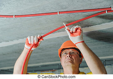 An electrician is fixing an electric corrugated tube. - An ...