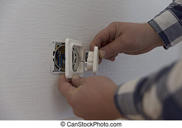 An electrician is installing contact. Home improvement