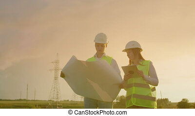 An electrician male and female in the fields near the power...