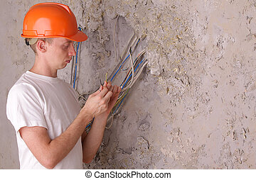 An electrician working in a repair house