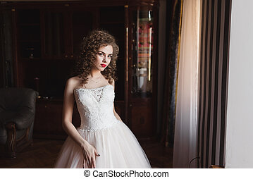 an elegant girl standing by the window dressed in a wedding dress she has curly hair