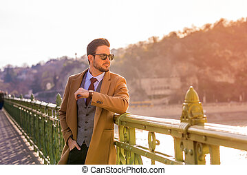 An elegant man standing on a bridge and checking the time