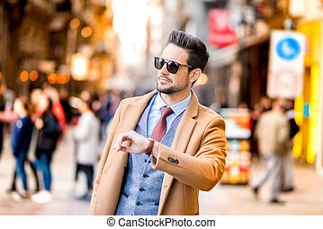 An elegant man walking on the streets and checking the time