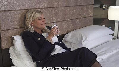 An elegant woman lies on the couch in her hotel room and drinks water
