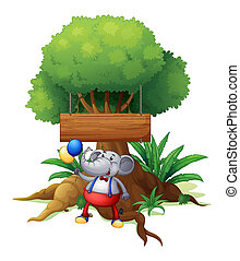 An elephant under the tree with a wooden signboard