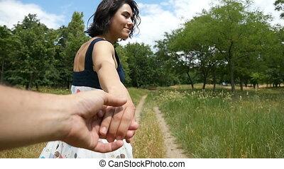 An emotional brunette girl runs along an alley,  pulls a hand of a man in slo-mo