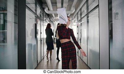 An emotional business woman dancing in office corridor...