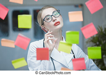 An emotional young doctor in the office, with a stethoscope around his neck in a white coat and a syringe in his hand, poses against a background of pasted colorful sticky notes to a transparent glass. Concept of medicine and healthcare.