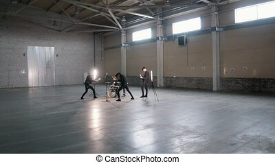 An emotional young group playing rock music in a big hangar....